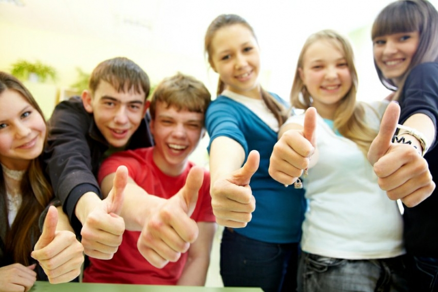 group of cheerful young students hands gesture shows OK in the classroom